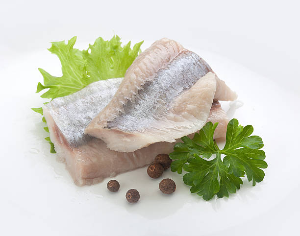 herring with lettuce and parsley - herring stock photos and pictures