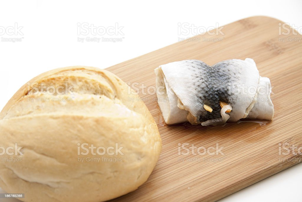 Herring with roll on wooden plate royalty-free stock photo