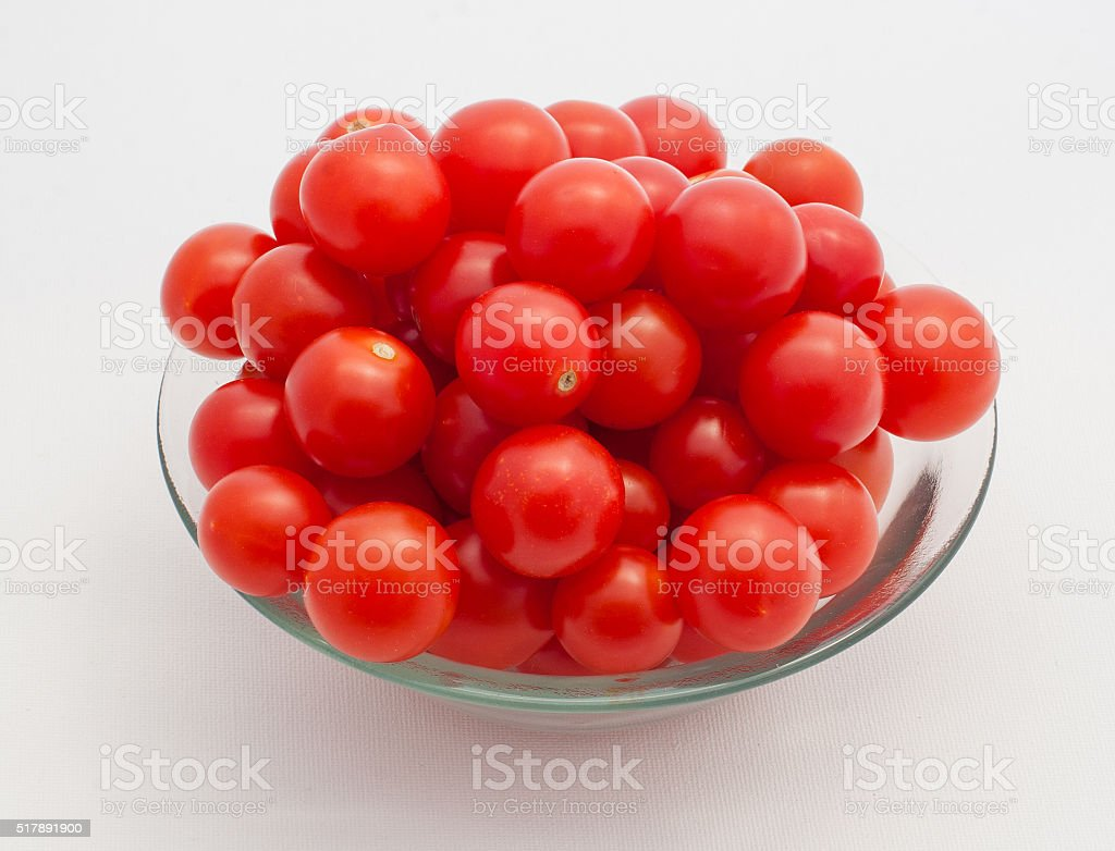 Сherry tomatoes in glass bowl on white background stock photo