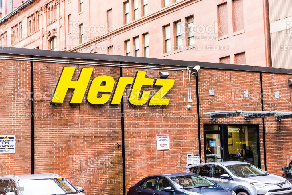 Hertz car rental sign and brick building in downtown area of city in Quebec region stock photo