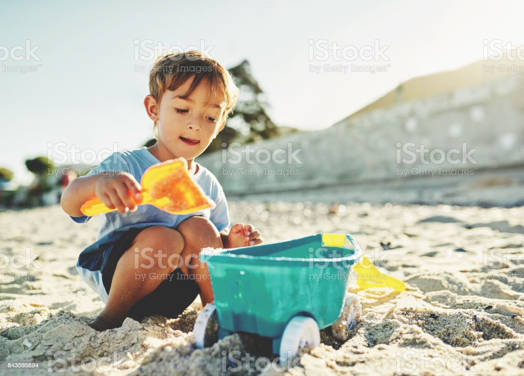 He's a boy who loves playing in the beach sand stock photo