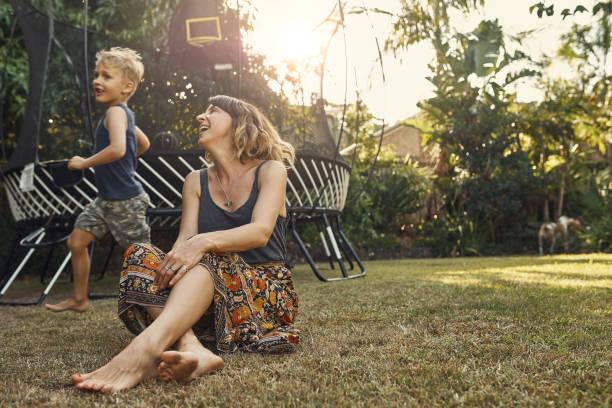 he's a bundle of energy - mãe criança brincar relva efeito de refração de luz imagens e fotografias de stock