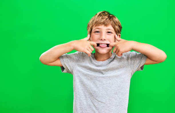 He's a cheeky little one Studio portrait of a young boy making a funny face against a green background protruding stock pictures, royalty-free photos & images
