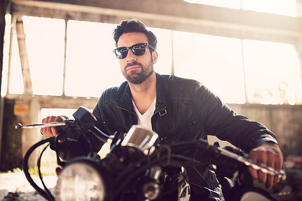 he's a hardcore rebel - motorrad männer stock-fotos und bilder