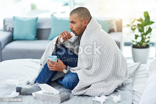 Full length shot of a young man sitting on his bed while feeling unwell at home