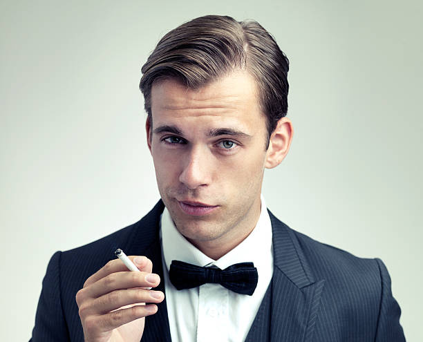 He's a man of sophistication A cropped portrait of a confident young gentleman smoking a cigarettehttp://195.154.178.81/DATA/shoots/ic_784009.jpg raised eyebrows stock pictures, royalty-free photos & images