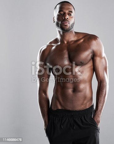 Studio shot of a muscular young man posing against a grey background