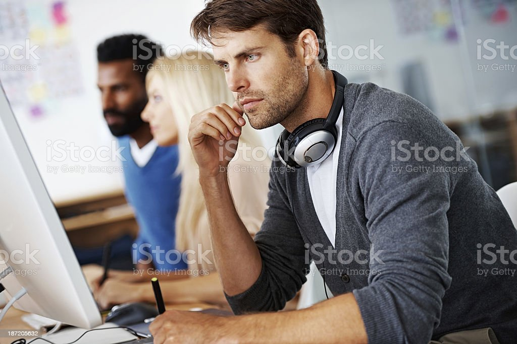 He's a perfectionist at work An employee concentrating on his work on his computer in a casual working environment 20-29 Years Stock Photo