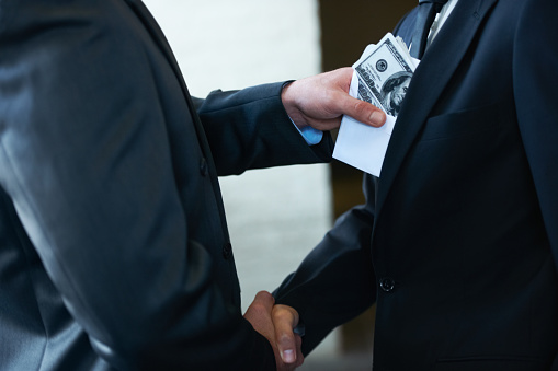 Two corporate businessmen shaking hands while one man places money in the other's pockethttp://195.154.178.81/DATA/i_collage/pi/shoots/781058.jpg