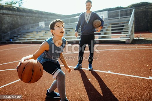 Photo of boy practicing is basketball with his coach