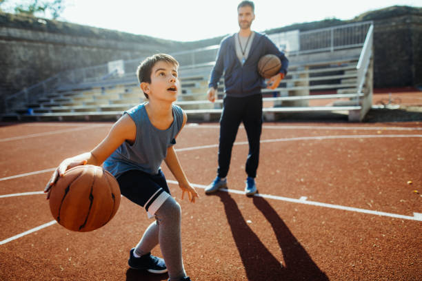 He's ahead of the game Photo of boy practicing is basketball with his coach basketball sport stock pictures, royalty-free photos & images