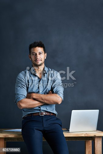Portrait of a handsome young businessman standing in front of a desk against a dark background