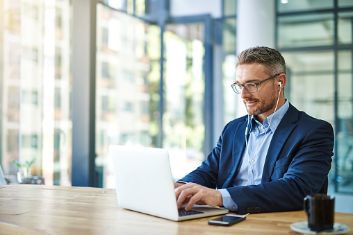 Shot of a mature businessman wearing earphones while using his laptop at work