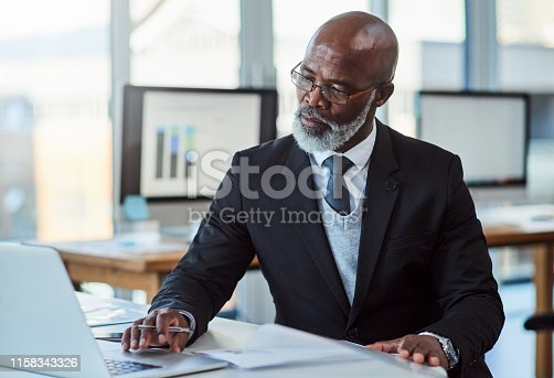 Shot of a mature businessman working on a laptop in an office