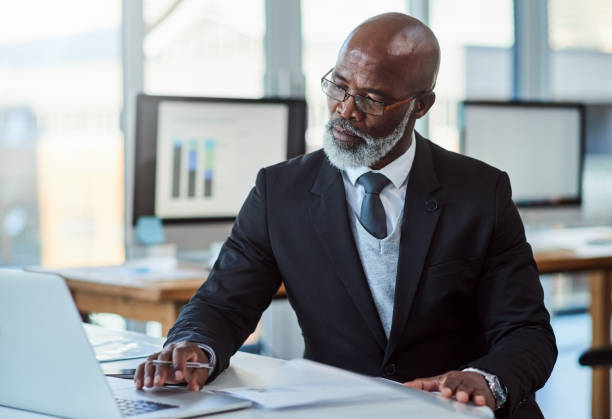 He's always a busy man Shot of a mature businessman working on a laptop in an office ceo stock pictures, royalty-free photos & images