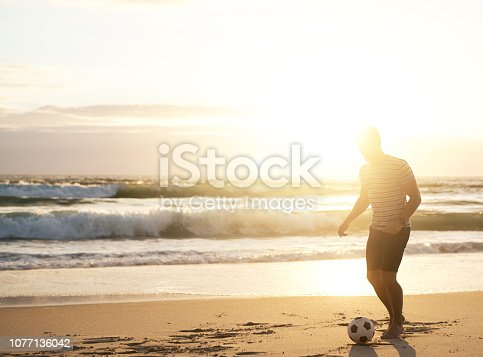 Shot of a young man playing with a soccer ball at the beach