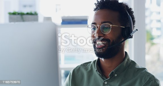 Shot of a handsome young businessman wearing headsets while working on a computer in his office