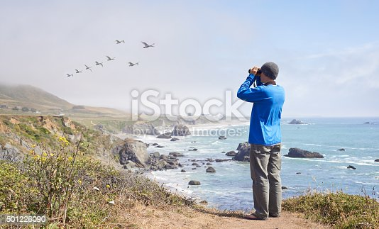 Shot of a young man standing on a hill by the ocean bird watchinghttp://195.154.178.81/DATA/i_collage/pu/shoots/806106.jpg