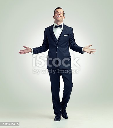 A full length studio shot of a confident young man wearing a vintage suit