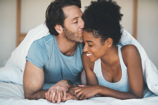 He's completely in love with her Shot of an affectionate middle aged man kissing his wife on her forehead while relaxing on their bed at home couple in bed stock pictures, royalty-free photos & images