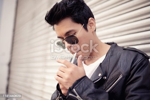 Shot of a handsome young man lighting his cigarette while out in the city