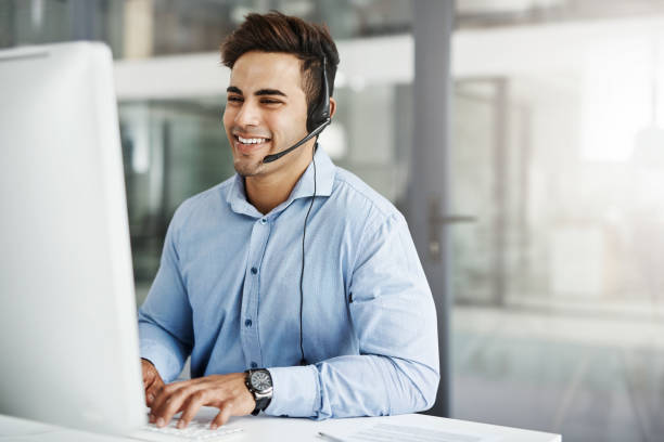 He's fluent in the company's brand Shot of a handsome young man working in a call center salesman stock pictures, royalty-free photos & images