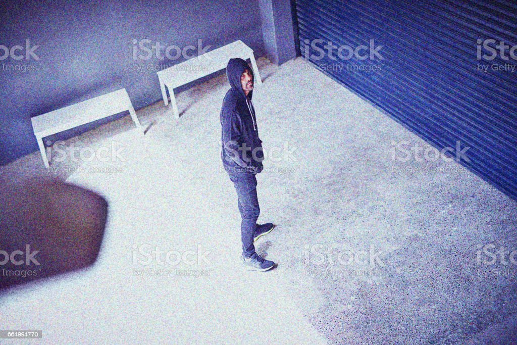 He's got crime on his mind High angle shot of a sketchy-looking man standing outside a building 20-29 Years Stock Photo
