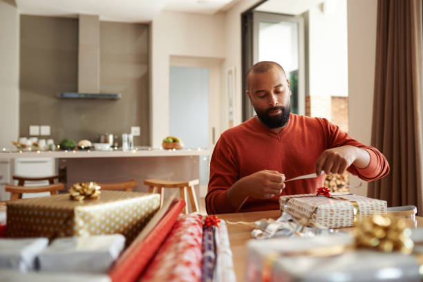 He's got gift wrapping duties covered Shot of a young man wrapping Christmas presents at home wrapping stock pictures, royalty-free photos & images