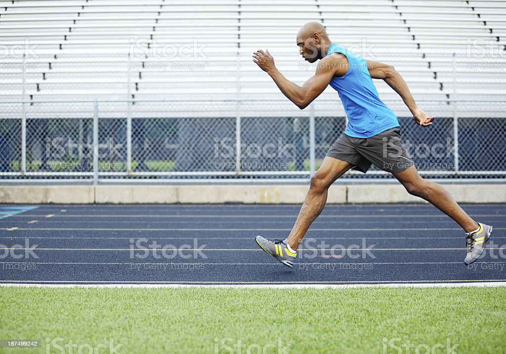 He's got grace and speed Full length side view of a male runner running on the track 40-49 Years Stock Photo