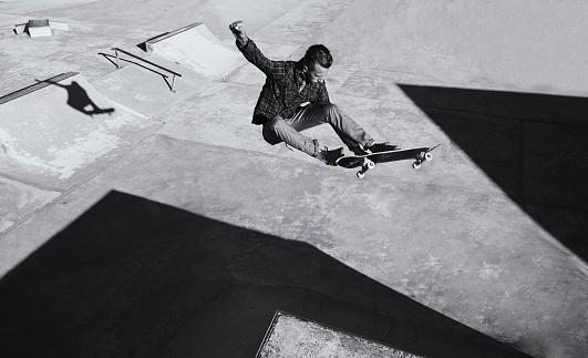 A black and white shot of a skateboarder doing tricks at a skatepark
