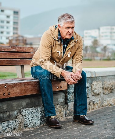 Full length shot of a senior man looking depressed while sitting on a bench near the beach