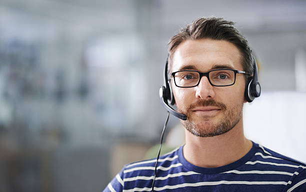 He's here to help! Portrait of a handsome young businessman wearing a headset in the office hands free device stock pictures, royalty-free photos & images