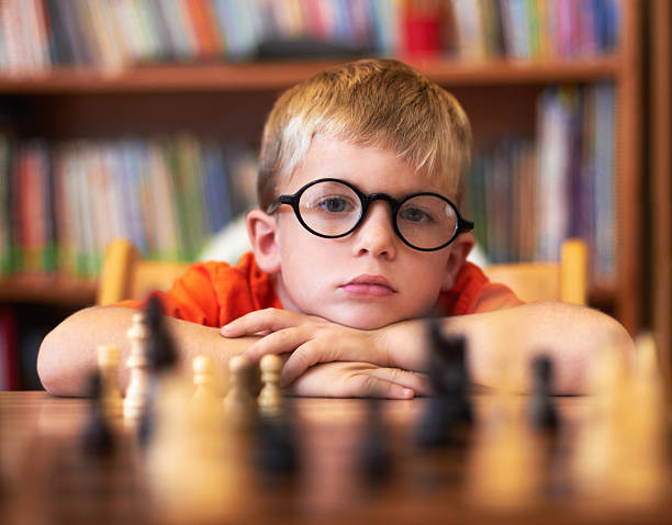 He's in need of better opponents! Young boy wearing spectacles and playing chess child prodigy stock pictures, royalty-free photos & images