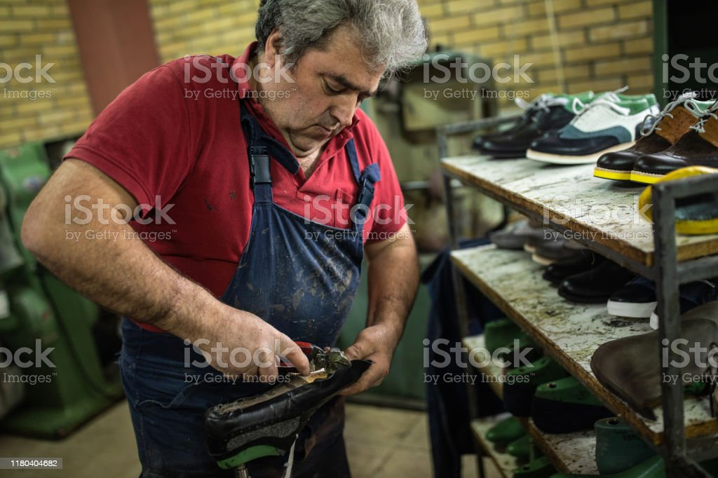 Overweight male manufacturing worker using hand tool for repairing...