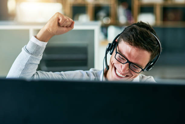 He's mastered the best way to sell the company's brand Shot of a young call centre agent cheering while working in an office salesman stock pictures, royalty-free photos & images