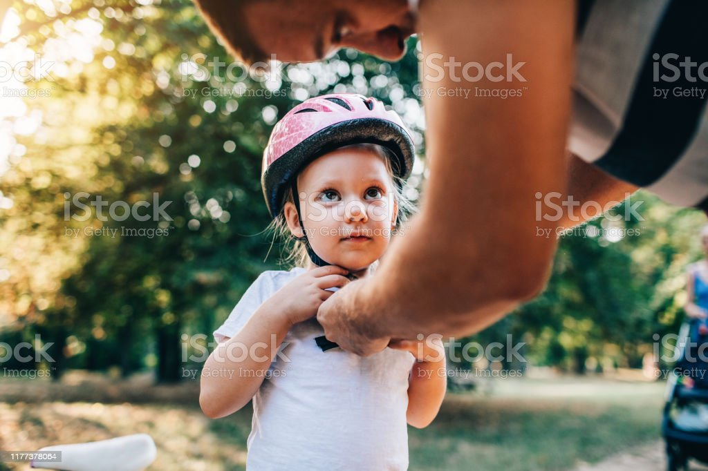 He's My Hero Father adjusting helmet to his little daughter and she looking at him. 30-39 Years Stock Photo
