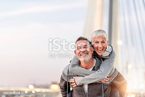 Photo of Happy mature couple having fun, hugging in the city on a autumn day. Love story true feelings concept. Portrait of friendly peaceful fitness couple in love. Couple enjoying the outdoors together. Sporty couple in love enjoying each other. Handsome  man giving a gray hair woman a piggy back ride.