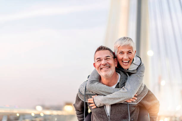 He's my solid rock! Photo of Happy mature couple having fun, hugging in the city on a autumn day. Love story true feelings concept. Portrait of friendly peaceful fitness couple in love. Couple enjoying the outdoors together. Sporty couple in love enjoying each other. Handsome  man giving a gray hair woman a piggy back ride. piggyback stock pictures, royalty-free photos & images