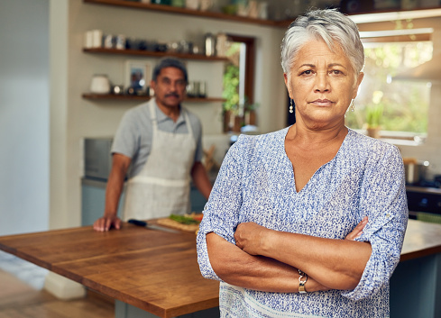 Portrait of a mature woman looking upset after a fight with her husband who is cooking in the background