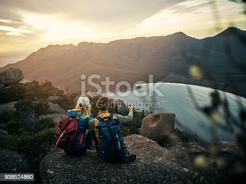 Rearview shot of a young couple taking selfies while sitting on a mountain peak
