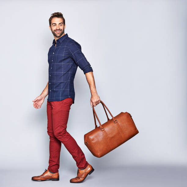 He's off on an adventure Studio shot of a handsome young man carrying a bag against a gray background menswear stock pictures, royalty-free photos & images
