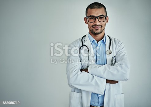 Studio portrait of a confident male doctor standing against a grey background
