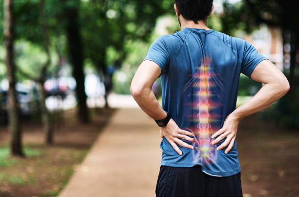 He's overdone it this time with his training Rear view shot of a sporty young man holding his back in pain while exercising outdoors spine body part stock pictures, royalty-free photos & images
