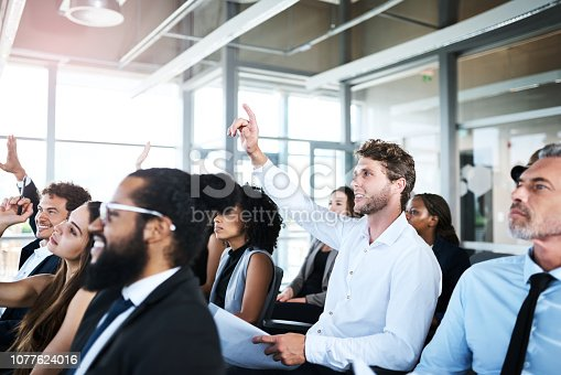 Shot of a young businessman raising his hand during a presentation in an office