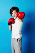Portrait of a young boy wearing boxing gloves in the studio
