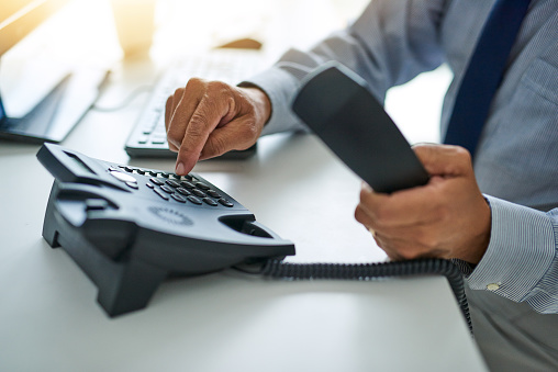 Cropped shot of an unrecognizable businessman dialing a number on a telephone at work