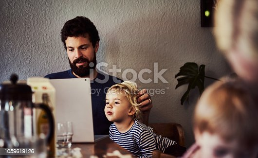 Cropped shot of a young man and his son using a laptop at the dining room table after having breakfast with the family