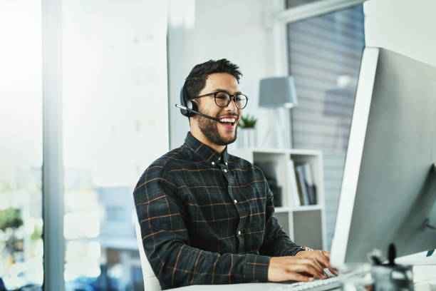 He's the guy with all the answers Shot of a handsome young call centre agent working in his office only young men stock pictures, royalty-free photos & images