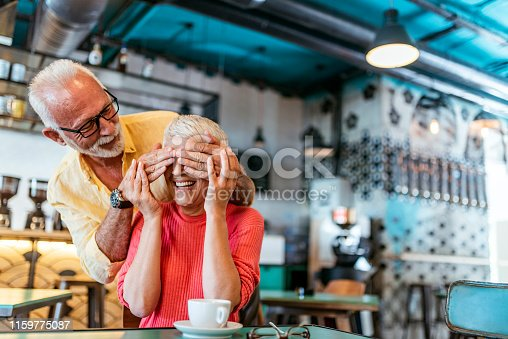 Photo of Cheerful senior loving couple having fun in the cafeteria during the day. Senior white hair man is standing behind awesome short hair woman and covering woman's eyes with hands. Oh come on, I know it's you. Beautiful old couple having a romantic time in the restaurant.