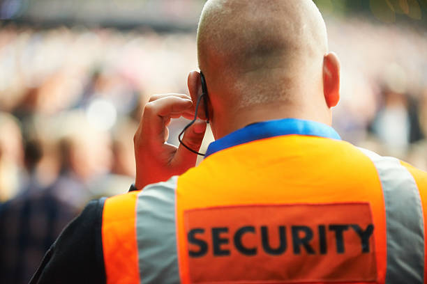 He's there for your protection Rear view of a security guard listening to his headset security staff stock pictures, royalty-free photos & images